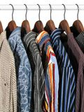 Colorful clothes on a rack. Choice of clothes of different colors in a closet. Isolated on white background royalty free stock photos