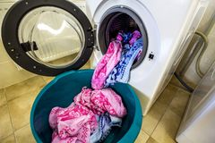 Colorful clothes and towels in washing machine drum.  Stock Photos