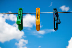 Colorful clothespin on a background of blue sky and white clouds Royalty Free Stock Photo