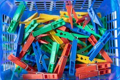 Colorful clothespins in a blue basket royalty free stock photo