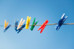 Colorful clothespins on clothesline against blue sky Royalty Free Stock Image