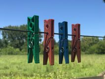 Colorful clothespins on a wire stock photo