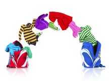 Colorful clothing fly out of backpack and falls into another bag. Colorful clothing fly out of backpack and falls into another backpack on white background Stock Images