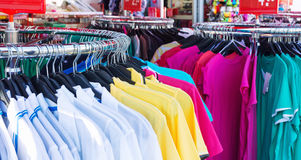 Colorful clothing on hangers Stock Images