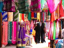 Colorful clothing for sale in India, with black-clad Muslim women royalty free stock photo