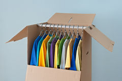 Colorful clothing in a wardrobe box for moving. Colorful clothing hanging in a wardrobe box, ready for moving Royalty Free Stock Photo