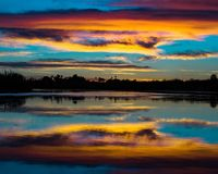 Cotton candy clouds over the mighty Colorado river. Colorful clouds floating above the Colorado river. mirrored onto the water perfectly stock photography