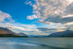 Colorful Clouds at golden hour on Lake Wakatipu at Glenorchy, NZ. Sunset view from Glenorchy wharf with colorful clouds moving against the beautiful mountain Royalty Free Stock Photos
