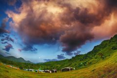 Colorful clouds over the huts in the mountains. royalty free stock photography