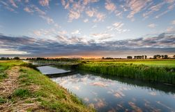 Bridge over a ditch in rural area at sunrise stock image