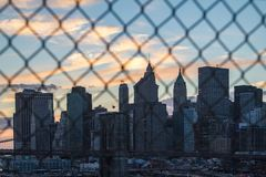 Sunset behind New York City Through Fence Stock Photo