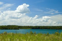Colorful cloudscape and lake. Colorful grass, lake, forest and cloudscape Stock Image