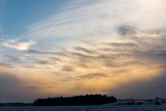 Colorful cloudy sunset at a snowy field with a some trees in the background on a cold day in winter royalty free stock photography