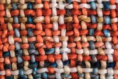 Colorful coarse woven cloth. Macro of a colorful coarse woven cloth with earthy colors stock images