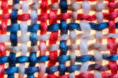 Colorful coarse woven cloth. Macro of a colorful red white blue coarse woven cloth stock photo