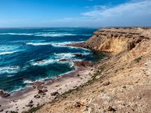 Colourful soft sea waves at rocky sea shore. Colorful coastline soft sea waves at rocky sea shore tall headland royalty free stock image