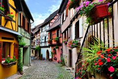 Colorful cobblestone lane in an Alsatian town, France. Quaint colorful cobblestone lane in the Alsatian town of Eguisheim, France royalty free stock photos