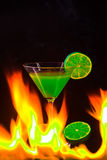 Colorful cocktail in nice green color to front of a black background and  fire Royalty Free Stock Image