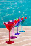 Colorful cocktail in a row with cherry on tropical sand beach Stock Images