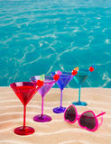 Colorful cocktail in a row with cherry on tropical sand beach Stock Photography
