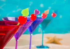 Colorful cocktail in a row with cherry on tropical sand beach Royalty Free Stock Photos