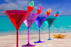Colorful cocktail in a row with cherry on tropical sand beach Royalty Free Stock Image