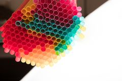 Colorful cocktail straws on black and white background overhead royalty free stock image
