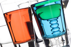 Colorful cocktails. Colorful drinks on a reflective tabletop against white background stock photography