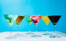 Colorful cocktails against blue background. Summer refreshments royalty free stock photography