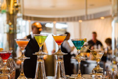 Colorful Cocktails in a Bar. With Bartenders and Patrons in Background royalty free stock image