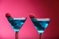 Colorful cocktails garnished with berries, studio shot. With copy space stock image