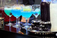 Colorful cocktails with ice on nightclub bar counter. Still life with many colorful cocktails with ice in wine glasses on cafe bar counter closeup royalty free stock image