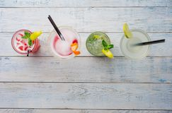 Colorful cocktails. Mojito, Red Cocktail with ice and lime, Margarita, Cosmopolitan on wooden table close up . Stock Photos