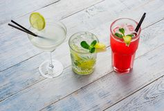Colorful cocktails. Mojito, Red Cocktail with ice and lime, Margarita on wooden table close up . Royalty Free Stock Photography
