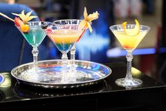 Colorful cocktails in restaurant bar counter. Still life with colorful cocktails in wine glasses  on round trays on bar counter front view closeup stock photography