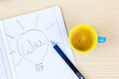 Colorful coffee cup with draw of bulb on paper Royalty Free Stock Image