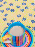 Colorful coffee cup on floral pattern table Royalty Free Stock Image