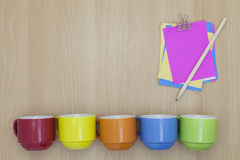Colorful coffee cup with paper note,pencil on wood background. Royalty Free Stock Photography