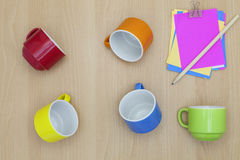Colorful coffee cup with paper note,pencil on wood background. Stock Image