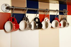Colorful coffee cups on hooks. Background Stock Photos
