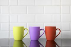 Colorful coffee mugs. On black granite kitchen table with their reflections on top of the counter's clean surface stock images