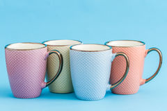 Colorful Coffee Mugs on Blue Background Stock Photo