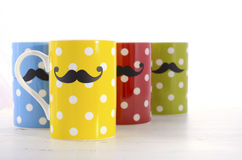 Colorful coffee mugs with mustaches. Royalty Free Stock Photo