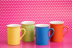 Colorful Coffee Mugs on Pink Background with White Dots Stock Image