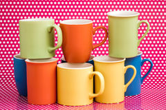 Colorful Coffee Mugs on Pink Background with White Dots Royalty Free Stock Images
