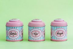 Colorful Coffee, Tea, Sugar Tin Storage Containers. On green Royalty Free Stock Images