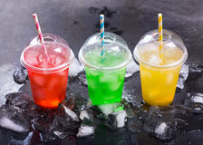Colorful cold drinks in plastic cups with ice. On dark background royalty free stock images