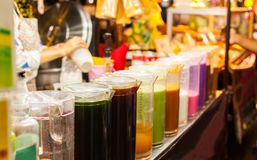 Colorful Cold Thai Milk Ice Tea in jugs on the street food market stall. Traditional Thai Beverage made with milk, sugar and tea.  Royalty Free Stock Images