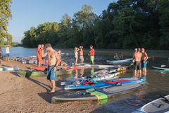 A colorful collection of paddle boards and people stock photo