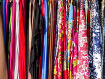 Colorful Collection of Tightly Packed Clothing on Rack. A collection of clothes and fabric tightly packed on a rack create a rainbow pattern Stock Photos